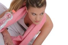 Fitness - young sportive woman with water and towel Stock Photos