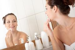 body care series - young woman cleaning her face in the bathroom - stock photo