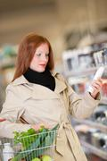 Shopping series - red hair woman buying shampoo Stock Photos