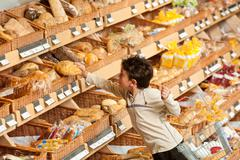 Grocery store shopping - little boy buying bread Stock Photos