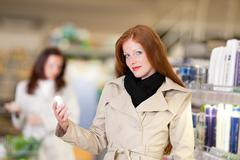 Shopping series - red hair woman holding deodorant Stock Photos
