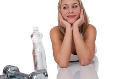 Fitness series - attractive woman with weights and bottle of water Stock Photos