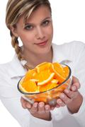 Stock Photo of healthy lifestyle series - woman holding bowl of oranges