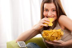 Stock Photo of student series - young woman eating potato chips