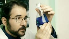 Male Scientist Looking at Flask (HD) Stock Footage