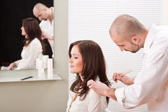 professional hairdresser comb customer at salon - stock photo