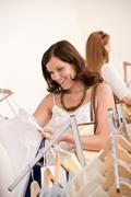 Stock Photo of fashion shopping - two happy woman choose sale clothes
