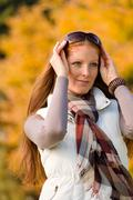 Stock Photo of autumn park - long red hair woman fashion