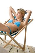 beach - young woman in bikini sitting on deck chair - stock photo