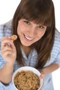 Stock Photo of smiling female teenager eat healthy cereal for breakfast