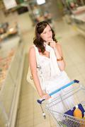 grocery store - thoughtful woman shopping - stock photo