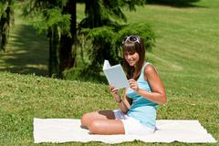 Stock Photo of smiling young woman read book in park