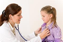 female doctor examining child with stethoscope - stock photo