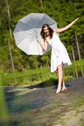 happy romantic woman with parasol in sunlight - stock photo