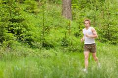 morning run: young man jogging in nature - stock photo