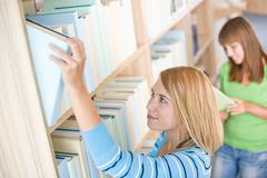 student in library - two woman search for book - stock photo
