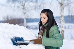 winter car - woman remove snow from windshield - stock photo