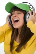 happy female teenager enjoy music with headphones - stock photo