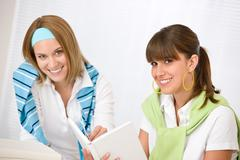 Stock Photo of student at home - two young woman study together