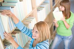 student in library - two woman choose book - stock photo