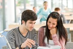 Stock Photo of two students read book in classroom