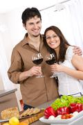 happy couple drink red wine in modern kitchen - stock photo
