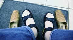 Mans feet in summer shoes and old pair stand near on carpet Stock Footage