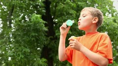 Little boy stands under rain and blows soap bubbles near tree Stock Footage