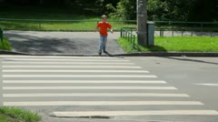 Boy looks around and walks over road by pedestrian crossing Stock Footage