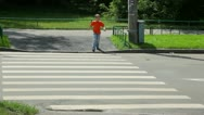 Stock Video Footage of boy looks around and walks over road by pedestrian crossing