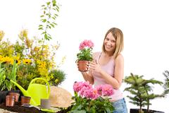 gardening - happy woman holding flower pot - stock photo
