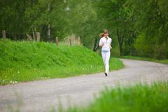 jogging - sportive woman running on road in nature - stock photo