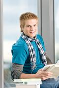 Young man with earbuds and books Stock Photos