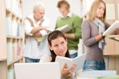 high school library - student with book - stock photo