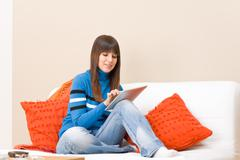 Teenager girl relax home with touch screen tablet computer Stock Photos