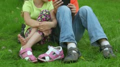 Two kids boy and girl sit together at grass near parking - stock footage