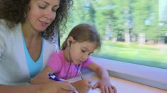 Little girl and mother draw by pens in book when sit at train Stock Footage