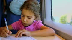 Little girl draws by pen on paper when sits at train near window Stock Footage