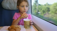 Little girl sits at table and mixes coffe near train window Stock Footage