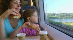 Mother with daughter eat marzipans and watch to train window Stock Footage