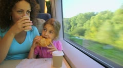 Mother drinks coffee and daughter eats when they travel in train Stock Footage
