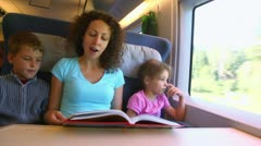 Mother reads book for children boy and girl when they travel Stock Footage