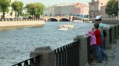 Mother with kids stand at quay and watch on ship float by river Stock Footage
