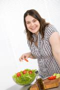 cook - plus size happy woman preparing salad in kitchen - stock photo