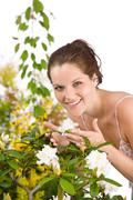 Stock Photo of gardening - woman with rhododendron flower blossom