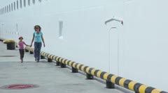 Mother with daughter walk by quay near board of huge liner Stock Footage