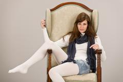 fashion model posing on antique armchair - stock photo