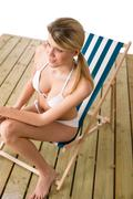 beach - woman in bikini sunbathing on deck chair - stock photo