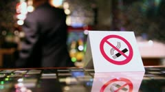 No smoking symbol on plate at table and man moves at background Stock Footage