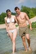 Stock Photo of happy couple in swimwear walk in lake